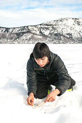 Charles Oudzi collects caribou scat on Tets'ehxe (Drum Lake) in the Shúhtagot'ı̨nę Nę́nę́ (Mackenzie Mountains) of the Northwest Territories, Canada. Caribou scat, collected non-invasively, provides genetic information that is used to analyze the connectivity and relationships between different caribou populations in the region. The research is dependent on the voluntary collection of scat samples by local hunters and trappers. Credit: Jean Polfus
